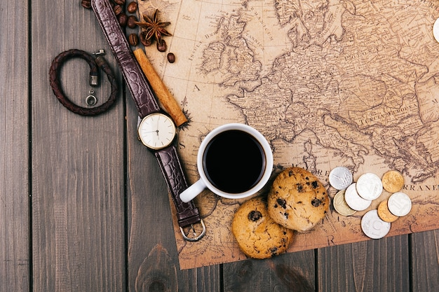 Cup of coffee, old yellow map, glasses, coins, leather case, camera, watch, compasses, coffee beans, other spices and cookies lie on wooden floor