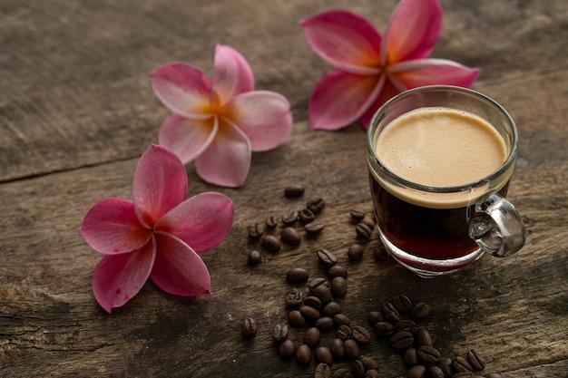 フランジパニの花と木製のテーブルの上のカップコーヒー。
