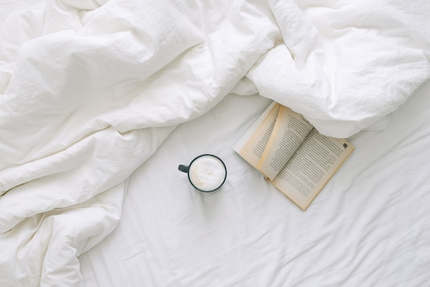 A cup of coffee and an open book lie on a white open bed. top view