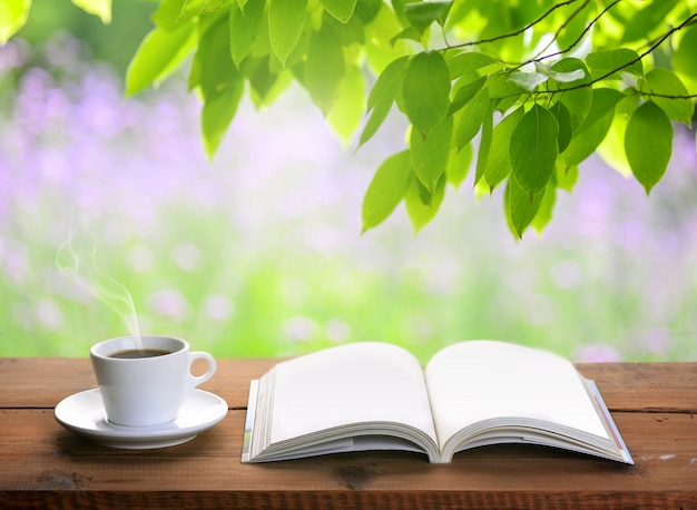 Cup of coffee and open book on wooden table