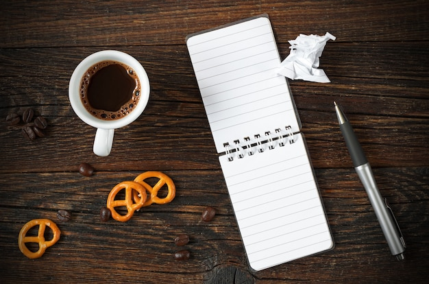 Cup of coffee and opened notepad with pretzel
