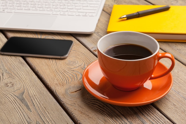 A cup of coffee on the orange plate on the wooden table. office interior