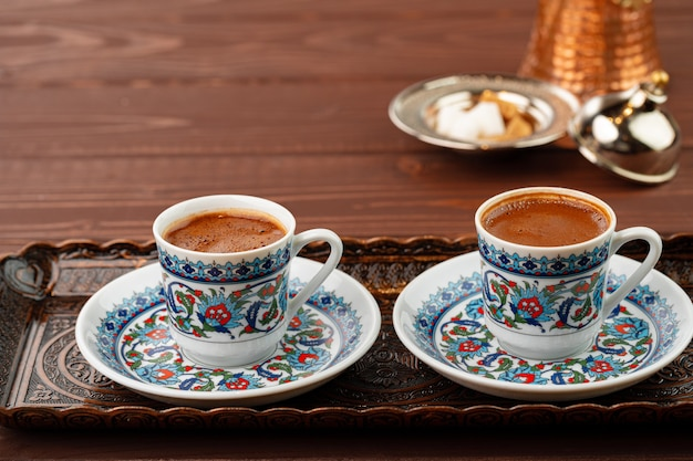 Cup of coffee in oriental style on metal tray close up
