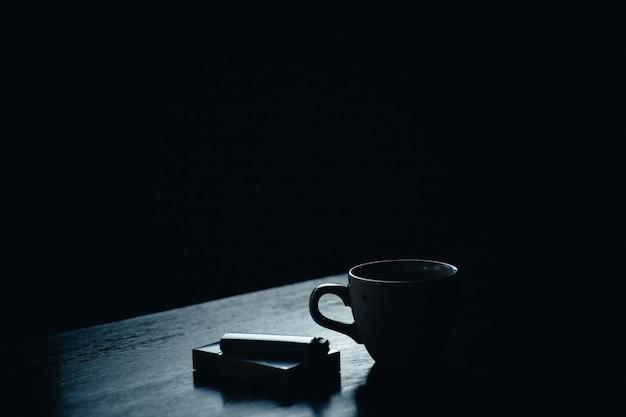 Tazza di caffè accanto a un pacchetto di sigarette e un accendino