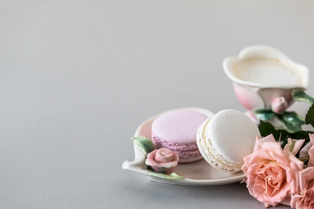 Cup of coffee, pasta for the cake and pink roses on a gray background. copy space.