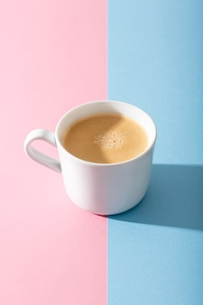 A cup of coffee on a pastel pink and blue background