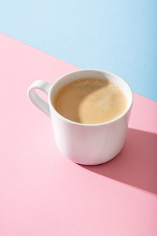 A cup of coffee on a pastel pink and blue background,