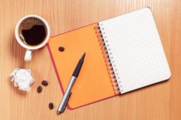 Cup of coffee, pen, notepad and crumpled paper on desk, top view