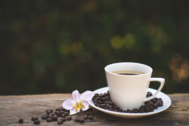 Чашка кофе, фалеанопсис на деревянный стол.