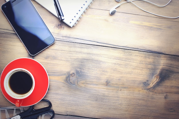 Cup of coffee, phone, earphone, notebook and pen on wooden