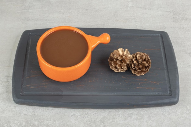 Cup of coffee and pinecones on dark plate.