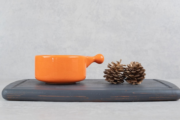 Cup of coffee and pinecones on dark plate
