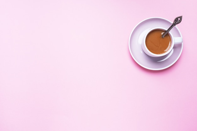 A cup of coffee on a pink background with copy space. top view. minimalism.