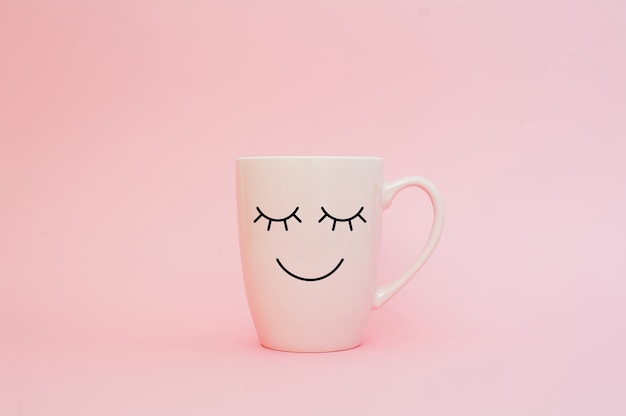 Cup of coffee on pink background with happy smile face