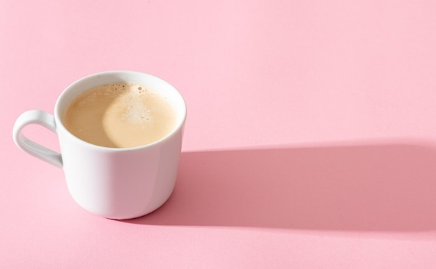 A cup of coffee on a pink background