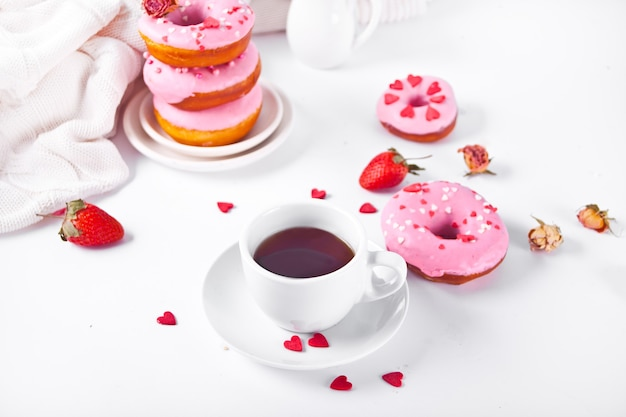 Cup of coffee and pink doughnuts