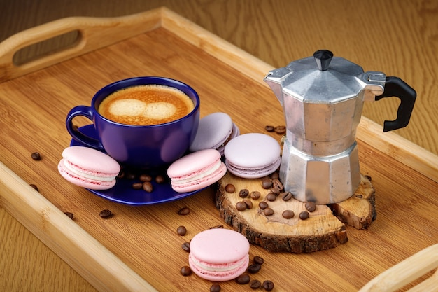 Cup of coffee, pink macaroons and coffee beans on a platter on a wooden tray