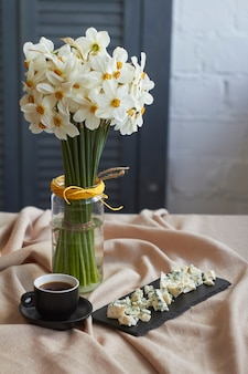 Cup of coffee and plate of cheese near large bouquet of white daffodils stands on table with beige linen tablecloth, holiday morning concept
