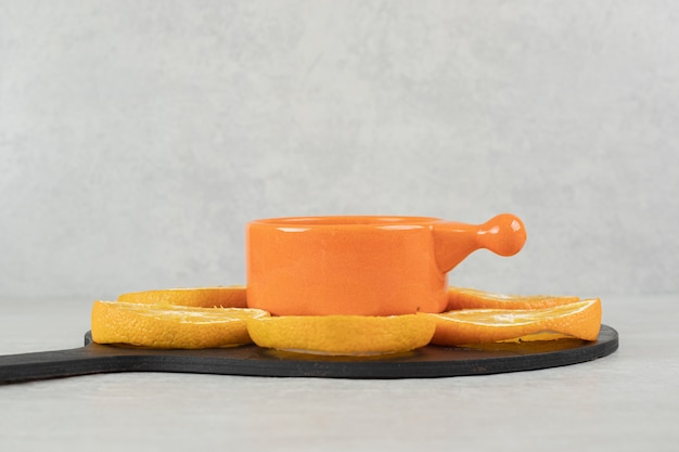 Tazza di caffè e piatto di fette d'arancia su tavola scura