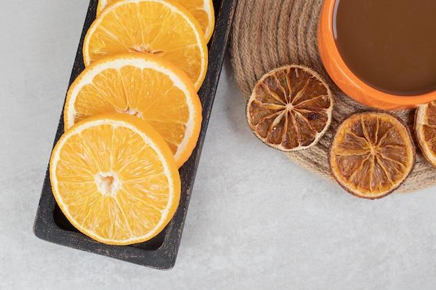 Tazza di caffè e piatto di fette d'arancia