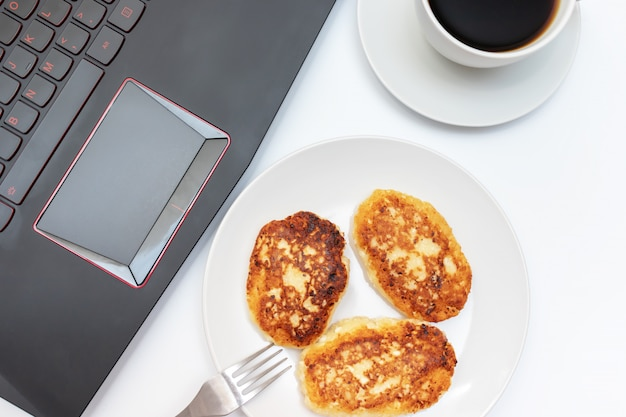 Cup of coffee and a plate with curd, cottage cheese pancakes for breakfast on the table near the laptop