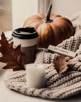 Cup of coffee, pumpkin, dried autumn leaves on window.