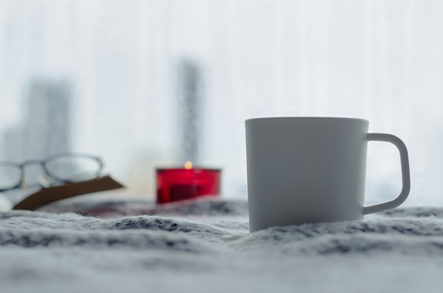 A cup of coffee puts on bed with aroma candle and book in winter season with blurred city background. zen and relax concept.
