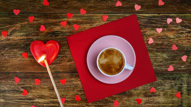 Cup of coffee on red napkin and set fire heart-shaped candle with long match. a romantic day.