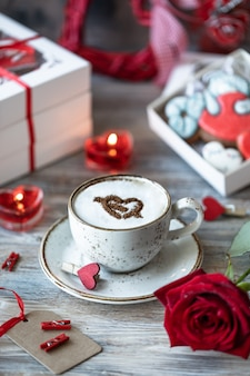 Cup of coffee, red rose and gift boxes