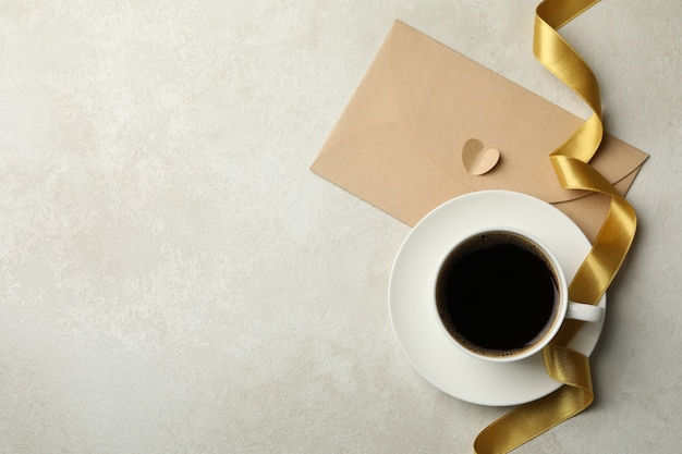 Cup of coffee, ribbon and envelope on textured background