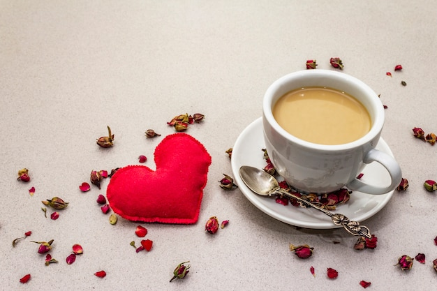 Cup of coffee, rose buds and petals and red felt heart