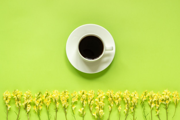 Cup of coffee and row yellow wild flowerson green background concept good morning or hello spring