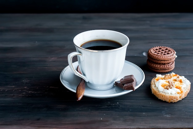 Cup of coffee, a sandwich with ricotta and cookies