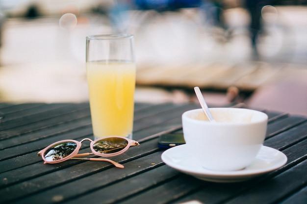 Tazza di caffè su un piattino con un succo d'arancia e un paio di occhiali da sole su un tavolo di legno