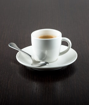 Cup of coffee on saucer with silver spoon