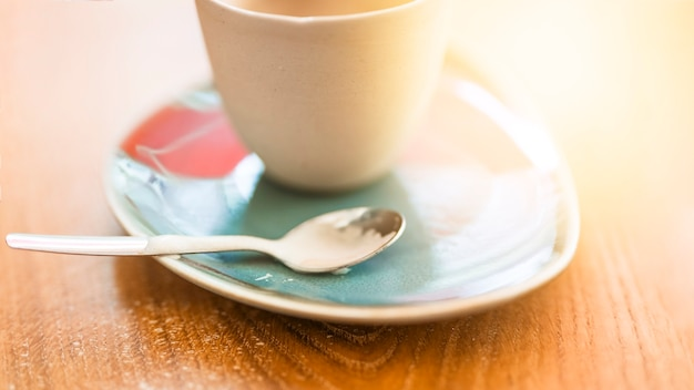 Cup of coffee on saucer with spoon over the wooden textured backdrop