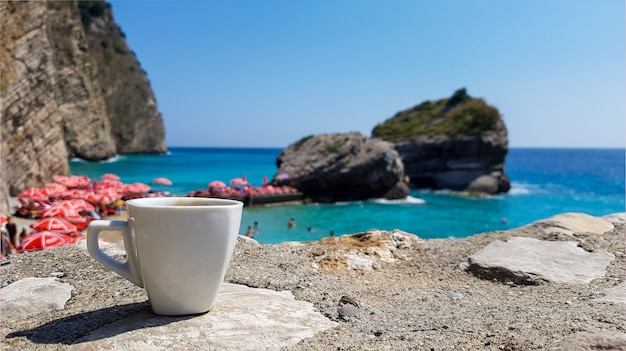 Cup of coffee on sea landscape, beach and horizon line, montenegro