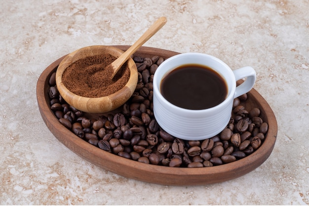 A cup of coffee and a small bowl of ground coffee powder on a pile of coffee beans in a tray