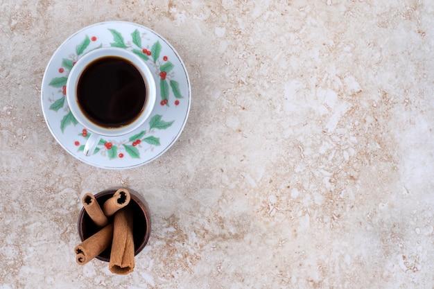 Una tazza di caffè e un mazzetto di bastoncini di cannella