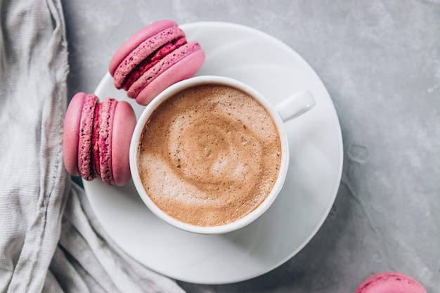 Cup of coffee and small macaroon cakes on gray concrete surface