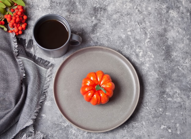Cup of coffee, small pumpkin on the concrete