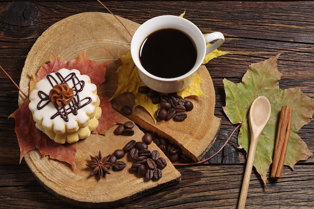 Cup of coffee, small round cake and autumn leaves on old wooden background
