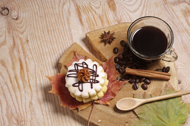 Cup of coffee, small round cake and autumn leaves on old wooden table