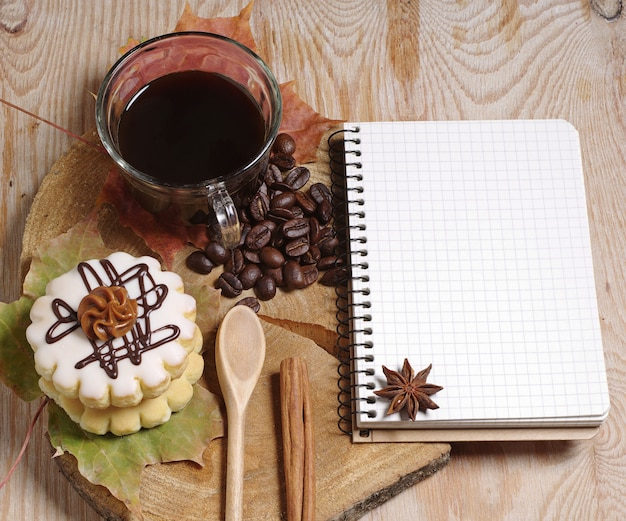Cup of coffee, small round cake and notebook on old wooden background