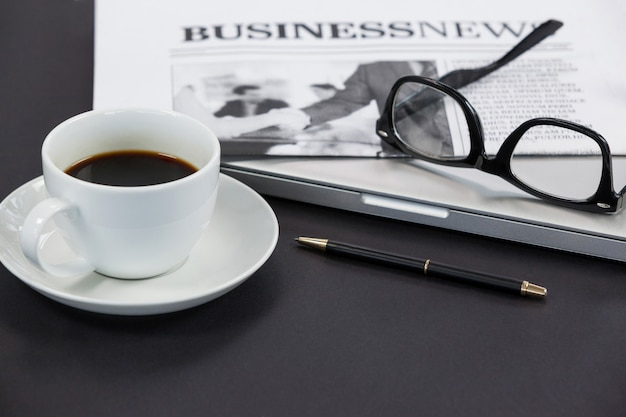 Cup of coffee, spectacles, closed laptop, newspaper and pen