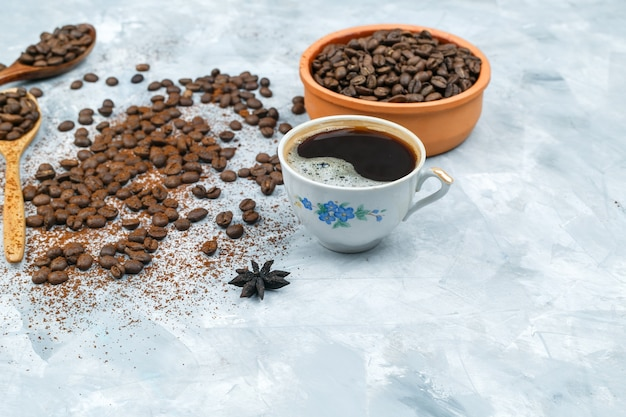 Cup of coffee, spices, and coffee beans in a bowl