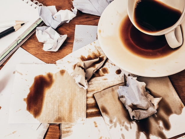Cup of coffee spilt on wood table, top view.