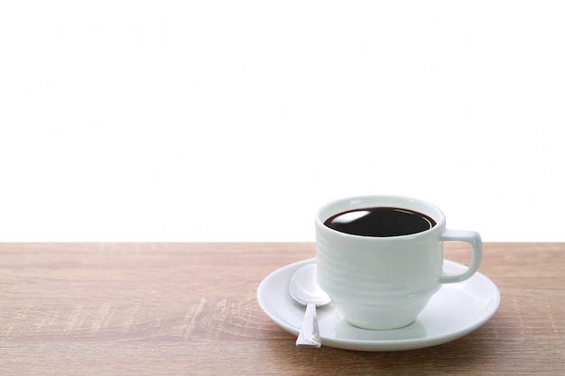 A cup of coffee and spoon on wood desk isolated