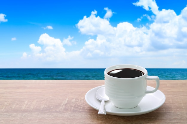 A cup of coffee and spoon on wood desk with beautiful beach