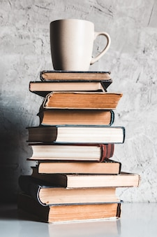 A cup of coffee on of stack of books on grey background. education, study, hobbies, read